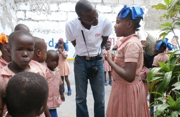 Philiogene at a school with children