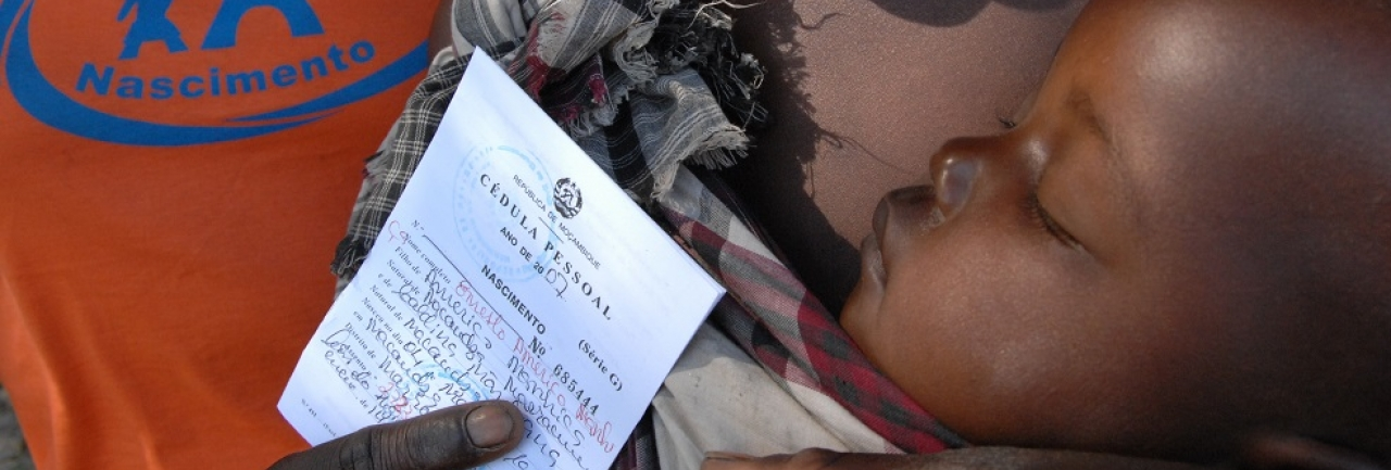 A woman holds her sleeping baby and his newly issued birth certificate