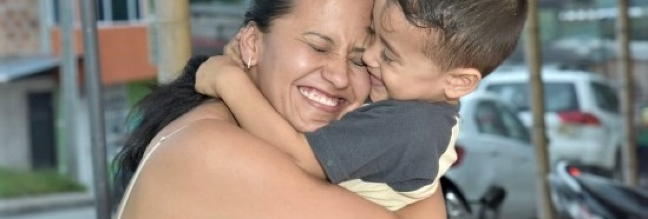 A mother and child engage in a joyful embrace in Bogota, Colombia