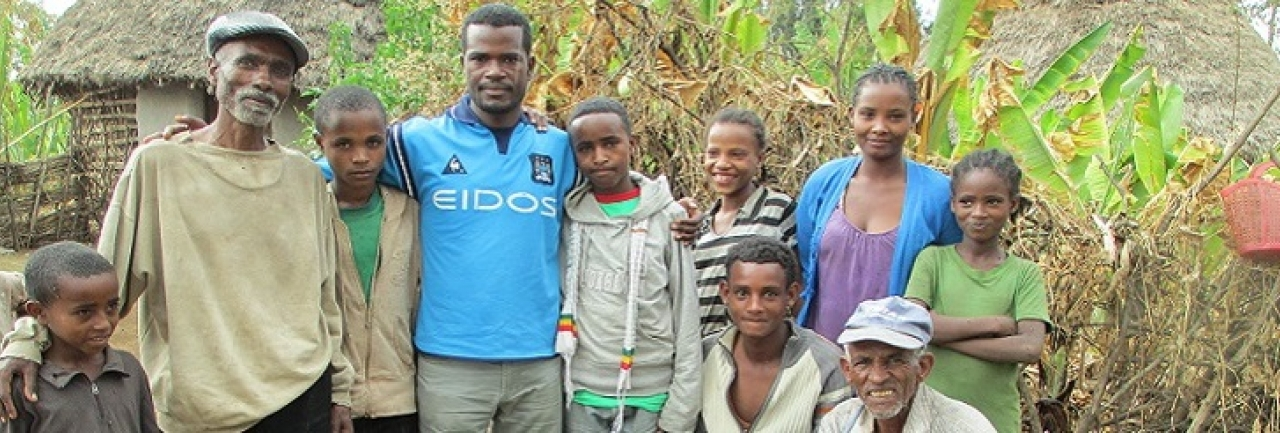A family in Ethiopia stands together outside their home